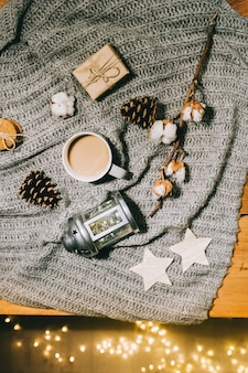 Flat lay christmas decorations. cup of coffee, a branch of cotton, a candlestick and cones on a gray knitted plaid