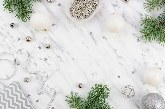 Flat lay christmas festive arrangement made of silver decorative elements and xmas branches