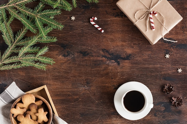 Flat lay of christmas fir tree branch, gingerbread man, coffee cup and computer or laptop keyboard on wooden background. top view winter, xmas and new year backdrop with space for text
