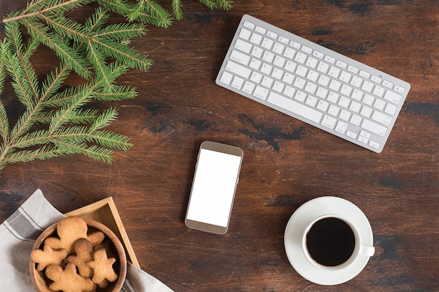 Flat lay of christmas fir tree branch, mobile phone, gingerbread man, coffee cup and computer or laptop keyboard on wooden
