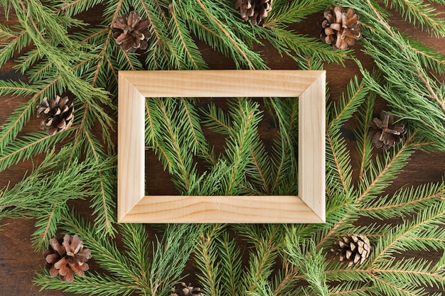 Flat lay of christmas fir tree branches on a wooden background with copyspace, view from above. wooden frame on the fir branches with a place for text