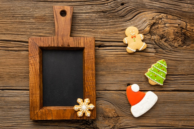 Flat lay christmas gingerbread cookies with small blackboard