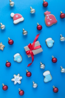 Flat lay of christmas gingerbread and gift box on the blue background. top view. location vertical.