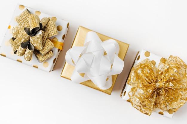 ゴールドカラーのギフトボックスと装飾が施されたフラットレイクリスマスまたはパーティーの背景。フラットレイ、上面図