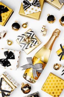 ギフトボックス、シャンパンボトル、弓、装飾、ゴールドとブラックのラッピングペーパーを備えたフラットレイクリスマスまたはパーティーの背景。フラットレイ、上面図