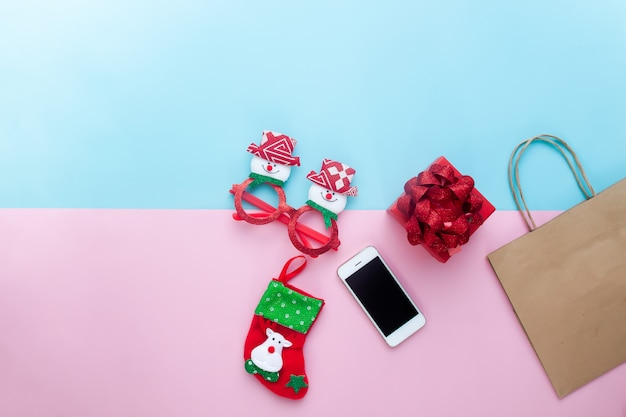 Flat lay of christmas ornaments with mobile phone and paper bag on colour background.