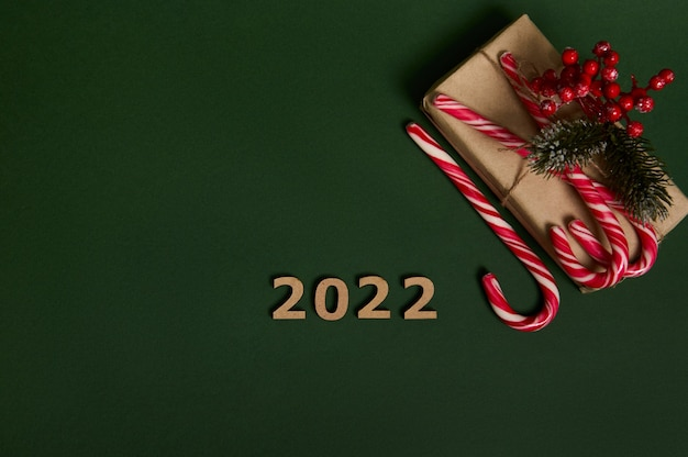 Flat lay of christmas present in craft wrapping paper decorated with holly and sugary striped lollipops candy canes and wooden numerals 2022 laid out in corner of copy space on dark green background