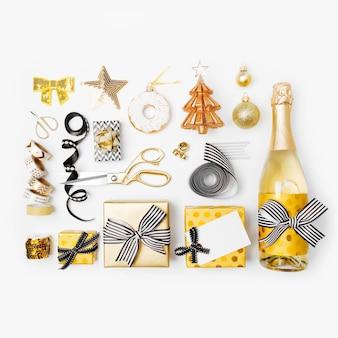 ギフトボックス、シャンパンボトル、リボン、デコレーション、ゴールドとブラックのラッピングペーパーがセットになったフラットレイクリスマス。フラットレイ、上面図