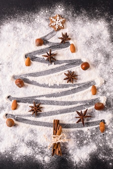 Flat lay of christmas tree shape with flour and star anise
