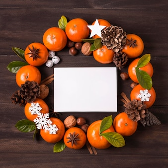 Lay piatto di ghirlanda di natale fare di mandarini e pigne con carta bianca