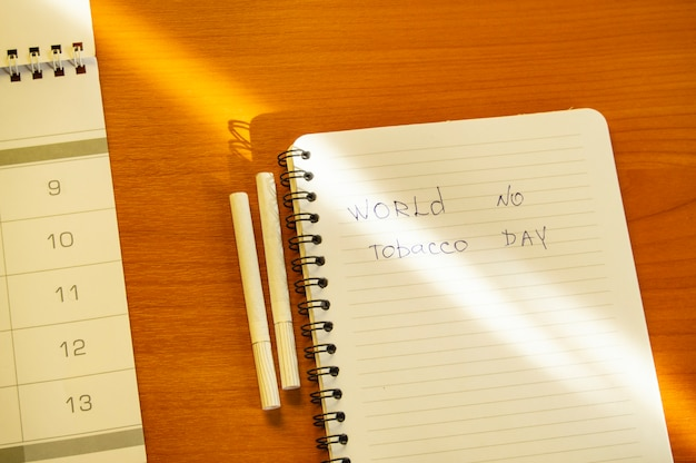 Flat lay, cigarettes and the inscription world no tobacco day written in a notebook