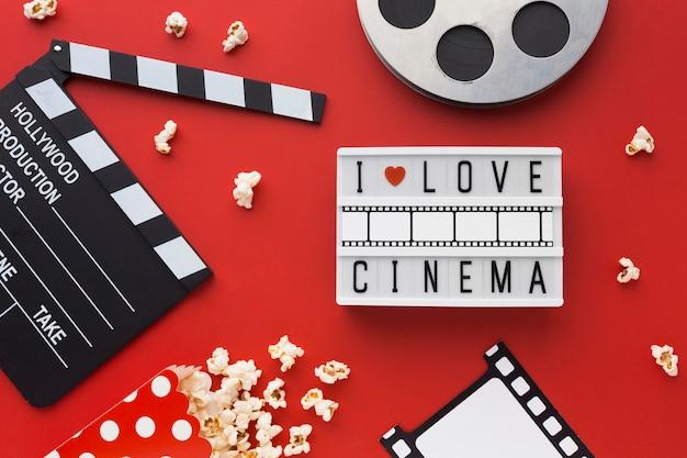 Elementi di cinema piatto laici su sfondo rosso