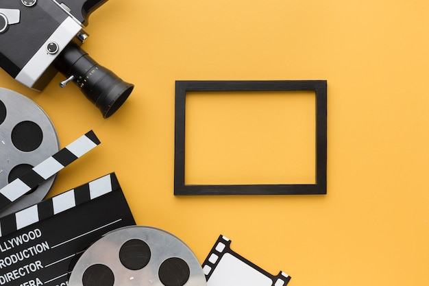 Flat lay cinema objects on yellow background with black frame