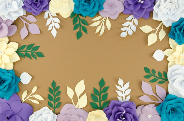 Flat lay circular frame with paper flowers and brown background