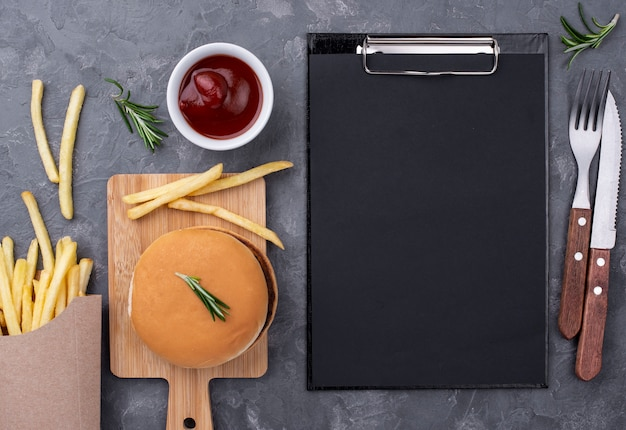 Flat lay clipboard beside hamburger and fries
