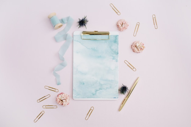 Flat lay of clipboard, rose buds, blue ribbon, golden pen and clips on pale pink