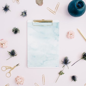 Flat lay of clipboard, rose buds, eucalyptus on pale pink