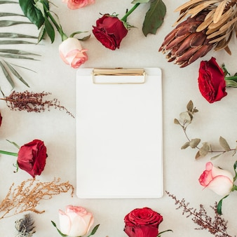 Flat lay clipboard with blank copy space for text in frame border of pink, red rose flowers, protea, tropical palm leaf, eucalyptus on beige surface