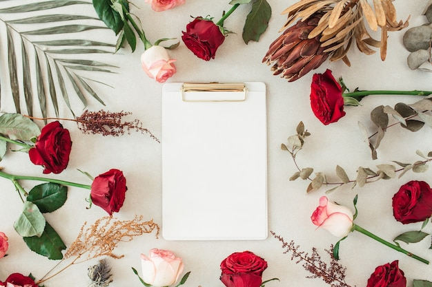Flat lay clipboard with blank copy space for text in frame border of pink, red rose flowers, protea, tropical palm leaf, eucalyptus on beige