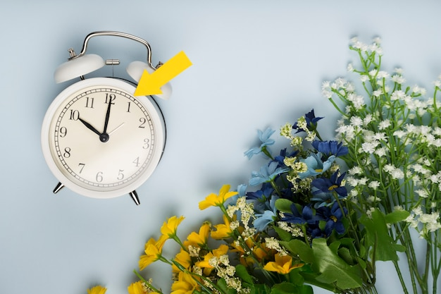 Flat lay clock beside bouquet of flowers