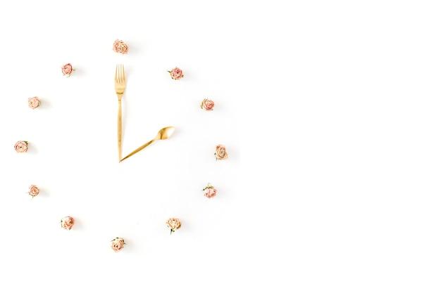 バラのつぼみ、スプーン、フォークで作られたフラットレイ時計の文字盤