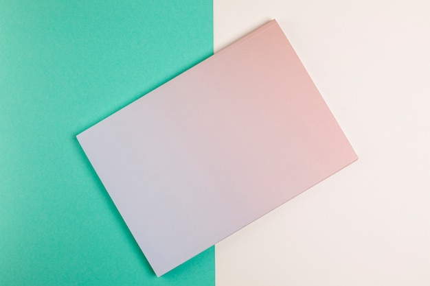 Flat lay closed book with colourful background