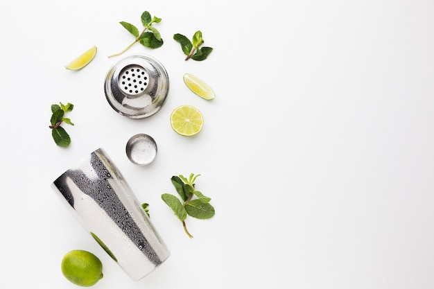 Flat lay of cocktail ingredients with shaker and lime slices