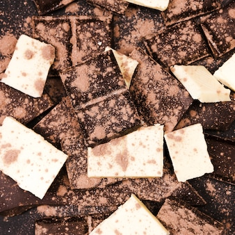 Flat lay cocoa powder covering dark and white chocolate