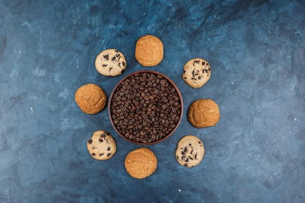 Chicchi di caffè piatti laici nella ciotola con diversi tipi di biscotti su sfondo blu scuro. orizzontale