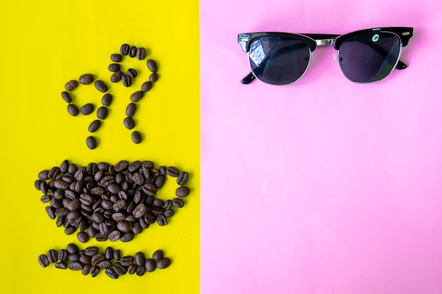 Flat lay coffee beans in coffee cup shape with sunglasses on sweet two tone background