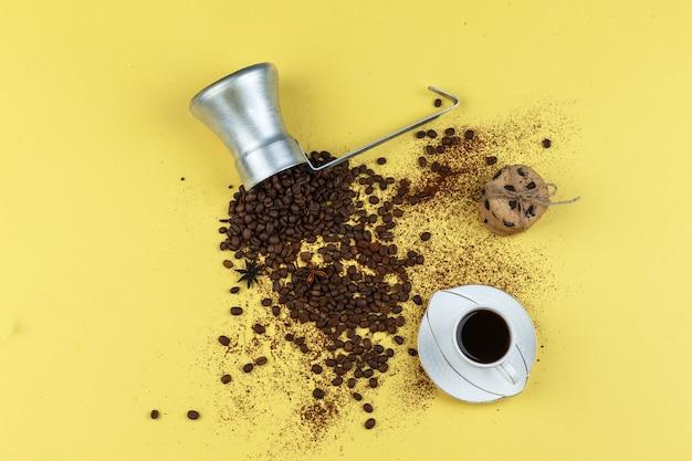 ガラスの瓶、一杯のコーヒー、黄色の背景にチョコレートチップクッキーと水差しのフラットレイコーヒー豆。水平