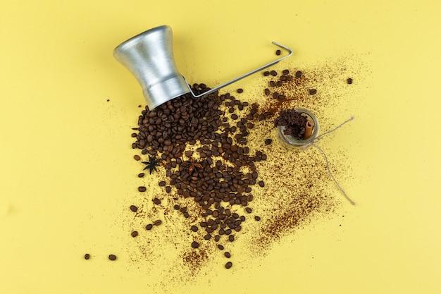 黄色の背景にガラスの瓶と水差しに平らなコーヒー豆を置きます。水平