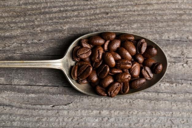 Плоские лежали кофейные зерна в ложке