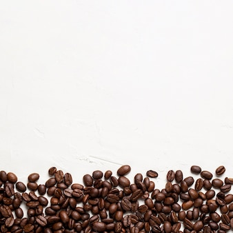 Flat lay coffee beans on white background with copy-space