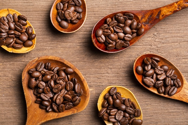 Flat lay coffee beans in wooden spoons