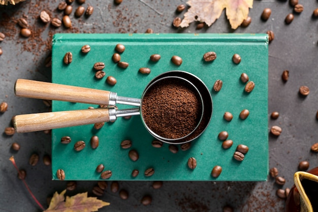 Flat lay coffee bowder in strainers on books