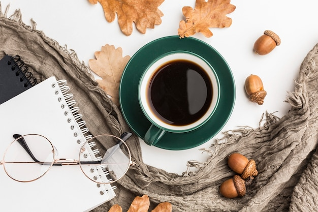 Flat lay of coffee cup with autumn leaves and notebooks