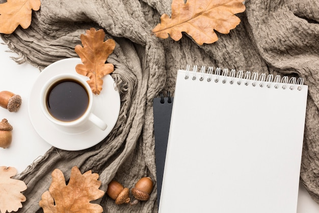 Flat lay of coffee cup with textile and autumn leaves