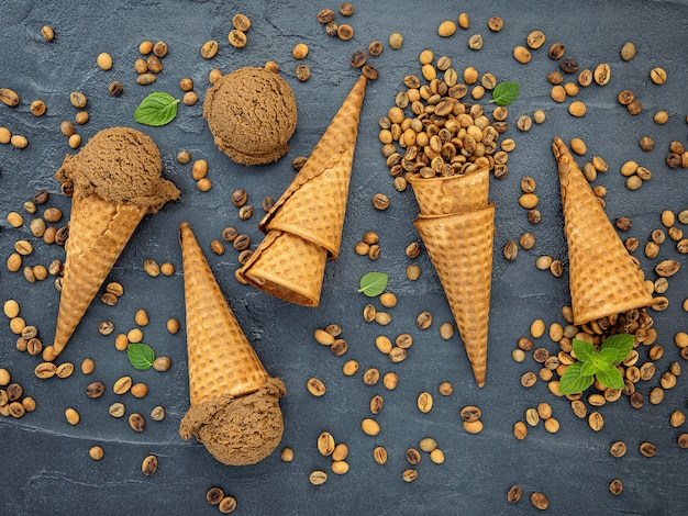 Flat lay coffee ice cream in waffle cone on dark stone background .