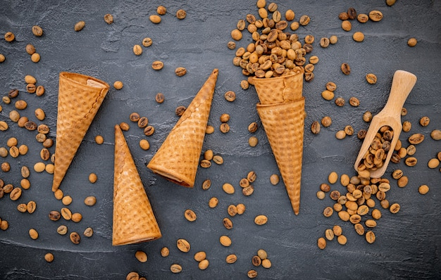 Flat lay coffee ice cream in waffle cone on dark stone background