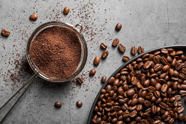 Flat lay coffee powder in strainer and coffee beans