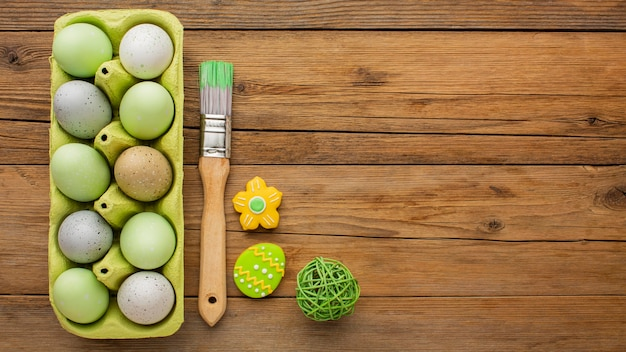 Flat lay of colored easter eggs in carton with paint brush and copy space