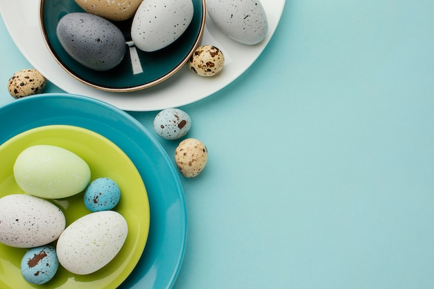 Flat lay of colored easter eggs on multiple plates