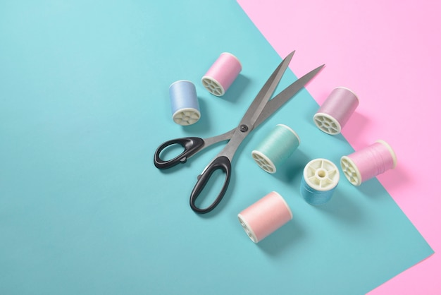 Flat lay of colored thread rolls and scissors for sewing, sewing and needlework concept.