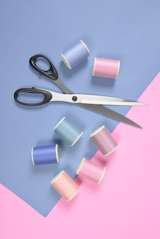 Flat lay of colored thread rolls and scissors for sewing on two tone background.