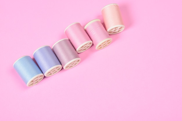 Flat lay of colored thread rolls for sewing on pink background.