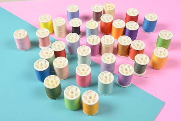 Flat lay of colored thread rolls for sewing on two tone background.