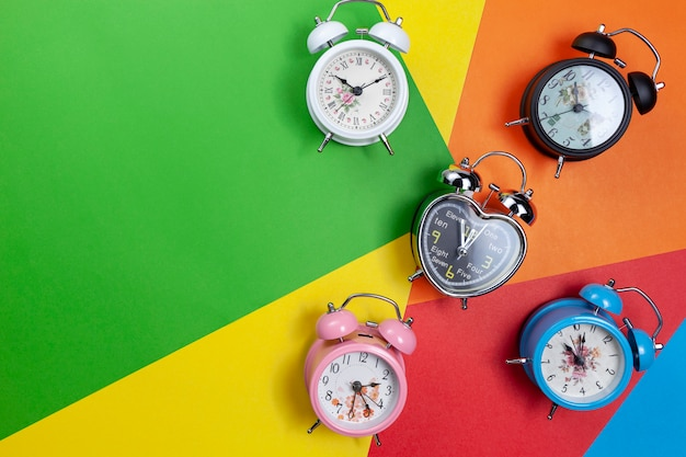 Flat lay of colorful alarm clock on beautiful paper background