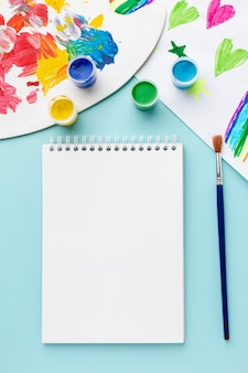 Flat lay of colorful aquarelle with notebook copy space