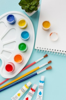 Flat lay of colorful aquarelle with notebook